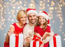 Happy family holding gift boxes and sparkles. Family, christmas and people concept - happy family in santa helper hats with many gift boxes and sparklers over Royalty Free Stock Image