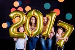Happy family holding golden balloons Stock Photo