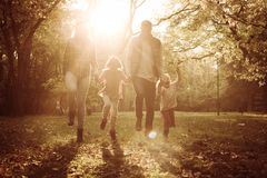 Family holding hands and jumping together trough park. Happy family holding hands and jumping together trough park royalty free stock photos