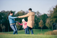 Happy family holding hands on meadow Stock Photo