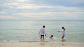 Happy family holding hands running along the shore. To run in the water creating splashes stock footage