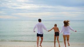 Happy family holding hands running along the shore. To run in the water creating splashes stock video