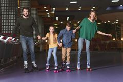 happy family holding hands while skating together stock images