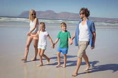 Happy family holding hands while walking at beach Stock Photos