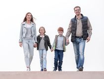 Happy family holding hands and walking. Isolated over white background stock photo