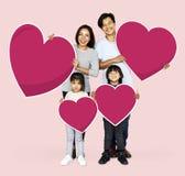 Happy family holding heart shapes royalty free stock photo