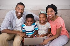 Happy family holding laptop while sitting on sofa at home Royalty Free Stock Photos