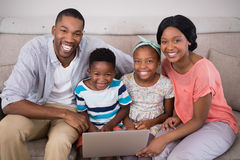 Happy family holding laptop while sitting on sofa at home. Portrait of happy family holding laptop while sitting on sofa at home royalty free stock images