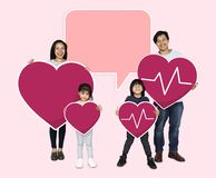 Happy family holding a pink heart icons royalty free stock photography