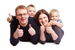 Happy family holding thumbs up. Happy family with two children holding their thumbs up Stock Photo