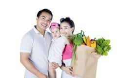 Happy family holds vegetables in studio Stock Image