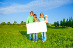 Happy family holds white square paper format Royalty Free Stock Photos