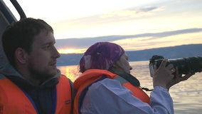 Happy family on holidays enjoying a boat ride down the lake during sunset. Female brunette traveler takes picture with stock footage