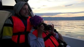 Happy family on holidays enjoying a boat ride down the lake during sunset. Female brunette traveler takes picture with stock video