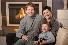 Happy family at home. Happy family sitting on couch at home in front of fireplace, looking at camera, smiling Royalty Free Stock Images