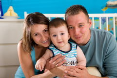 Happy family at home. Portrait of happy family at home. Baby boy ( 1 year old ) and young parents father and mother sitting on floor and playing together at stock photography