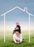 Happy family with home drawing. Happy family lying on grass field surrounded by home drawing Royalty Free Stock Photos