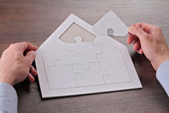 Happy family, home, insurance concept. Man building house shape blank puzzle Stock Photography