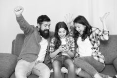 Happy family at home. Little girl use smartphone with mother and father. Family with happy mood. Happy family selfie stock photography