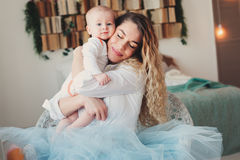 Happy family at home. Mother holding baby son in bedroom in cozy weekend Stock Photos