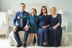 Happy family at home. Older woman, man, pregnant adult woman. Happy family at home. Older woman, man, pregnant adult women and child girl stock image