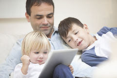 Happy family at home with tablet. Happy family, father and offsprings having fun at home with digital tablet Royalty Free Stock Images