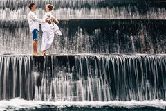 Happy family honeymoon holiday. Couple in cascade waterfall pool. Happy family on honeymoon holidays - married loving couple hugging, kissing with fun under Royalty Free Stock Photo