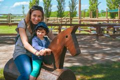Happy family horse ranch petting zoo trip background mother and baby child ride.  royalty free stock images