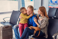 Happy family hugging at airport. I love you so much. Happy little boy hugging and kissing his father during waiting for registration Royalty Free Stock Photo