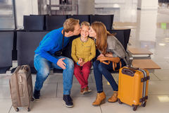Happy family hugging at airport. Picture of love and happiness.  of happy young parents kissing their son on his cheeks waiting for boarding while sitting at Stock Image