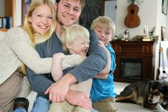 Happy Family Hugging in Living Room Stock Photography