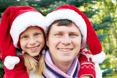 Happy family hugging near a Christmas tree on the street Stock Image