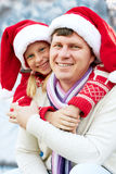 Happy family hugging near a Christmas tree on the street Stock Images