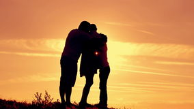 Happy family hugging silhouettes at sunset stock video footage