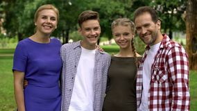Happy family hugging and smiling in park, posing into camera, pride for children royalty free stock image