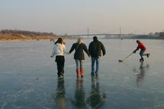 Happy family on ice. A family walking on the frozen river danube in vienna royalty free stock photography