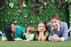 Happy family ie on grass near hedge with flowers. Happy family of four lie on grass near hedge with flowers in garden Stock Photos