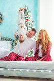 Happy Family In Plaid Pajamas Fooling Around Near The Christmas Tree. Mother, Father And Little Son Laughing On The Bed Stock Images