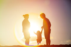 Happy family including pregnant mother, father and toddler at sunset. Happy family including pregnant mother, father and toddler play at sunset royalty free stock image