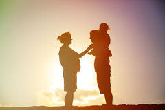Happy family including pregnant mother, father toddler at sunset. Silhouette of happy family including pregnant mother, father toddler at sunset royalty free stock image
