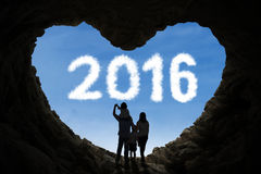 Happy family inside cave looking at numbers 2016 Royalty Free Stock Images