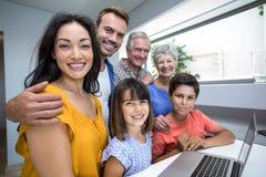 Happy family interacting using laptop Stock Photo