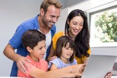Happy family interacting using laptop Stock Photos
