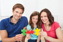 Happy family joining puzzle pieces Royalty Free Stock Images