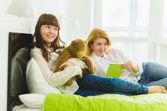 Happy family. joyful and dreaming daughter holding teddy bear lies beside mom Stock Photography