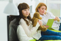 Happy family. joyful and dreaming daughter holding teddy bear lies beside mom Stock Image