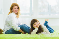 Happy family. joyful and dreaming daughter lies beside mom Stock Images