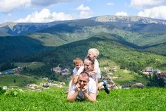 Happy family: joyful father, mother and two sons are lying on the green grass against the background of the forest, mountains and royalty free stock photography