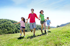 Happy family joyfully running in beautiful landscape Stock Photography
