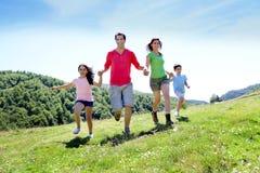 Happy family joyfully running in beautiful landscape Stock Photography